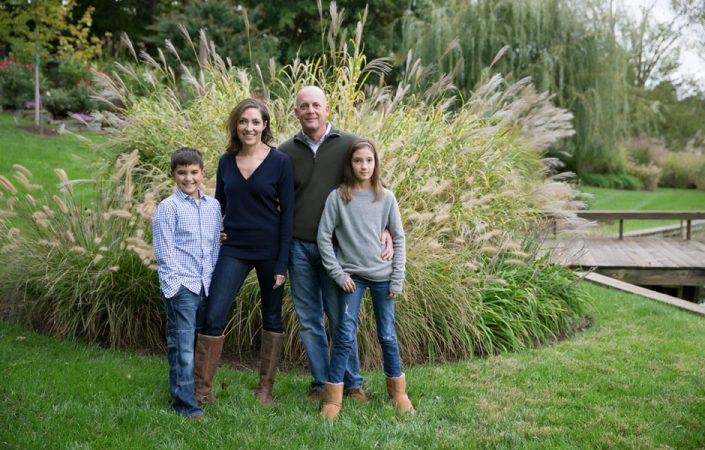 Couple with their children posing with bushes behind | Anne Lord Photography