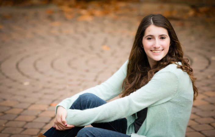 Teenage girl sitting on a brick floor   Anne Lord Photography