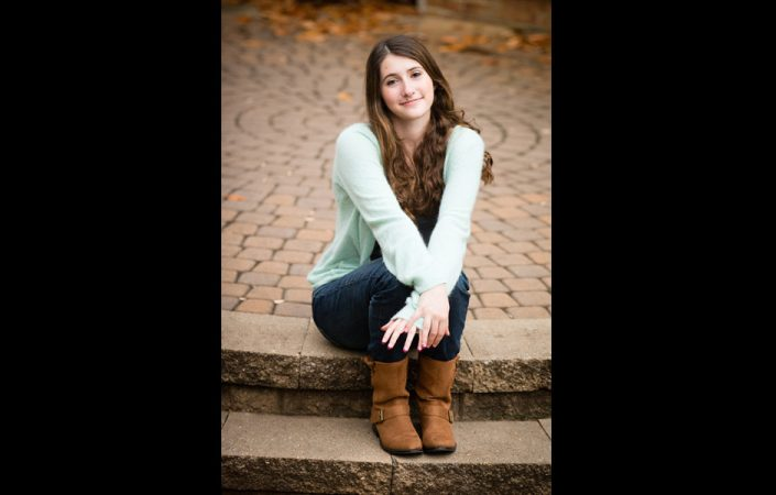 Teenage girl with angelic face sitting on bricked stairs   Anne Lord Photography