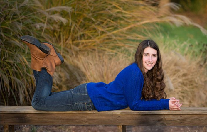 Curly long haired girl lying on the wooden bench   Anne Lord Photography