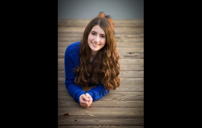 Brown curly haired girl laying on the wooden deck   Anne Lord Photography
