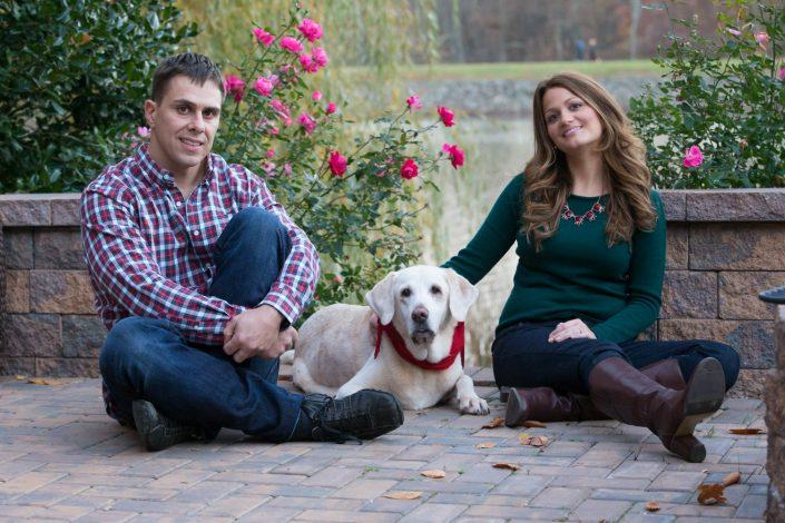 Couple sitting on a brick floor and dog laying in the middle | Anne Lord Photography