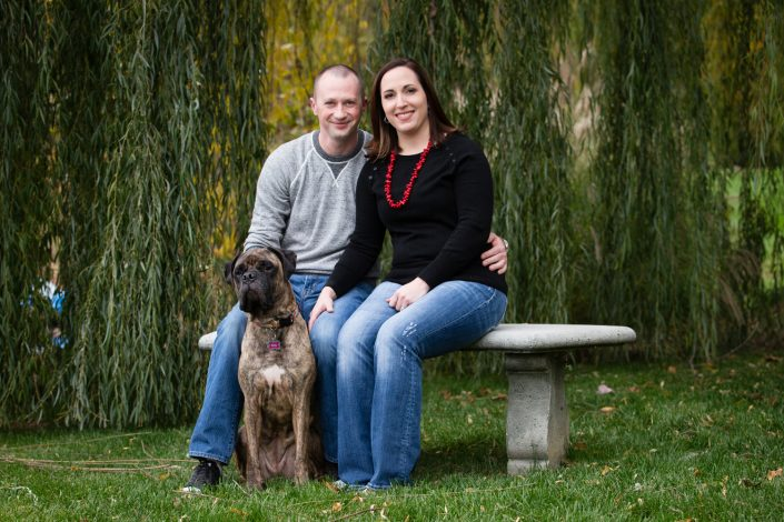 Happy Couple sitting in a stone bench while dog sitting on the grass | Anne Lord Photography