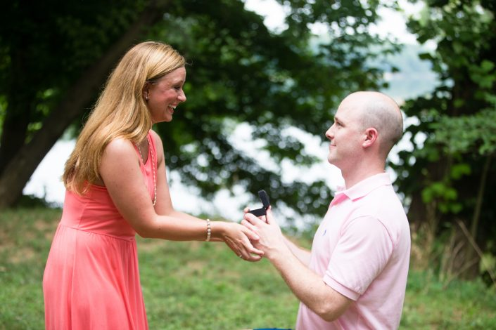Happy Couple guy on bended knees proposing wearing pink | Anne Lord Photography