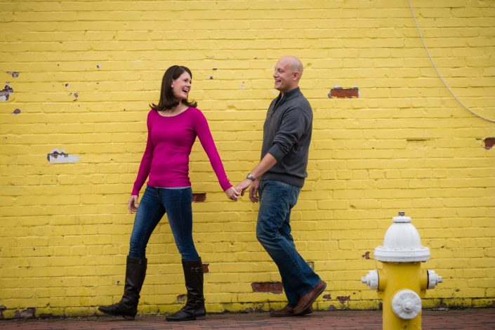 Couple holding hands with yellow bricked wall | Anne Lord Photography