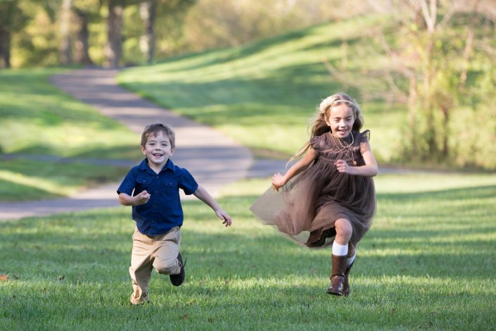 Little girl on brown dress and little boy wearing blue shirt running on the grass | Anne Lord Photography