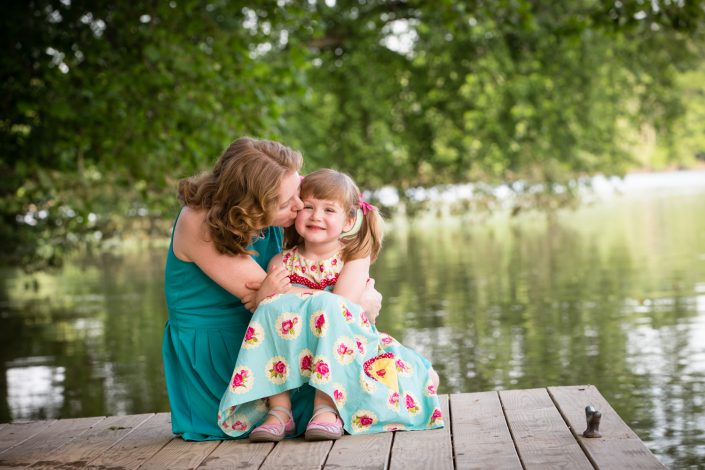 Mom sweetly kissing daughter by the lake | Anne Lord Photography